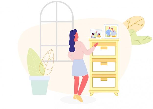 Vrouw familiefoto bekijken op dressoir, woonkamer