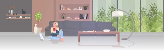 Vrouw freelancer koffie drinken werken op laptop thuis blijven coronavirus pandemie quarantaine concept moderne woonkamer interieur horizontaal volledige lengte