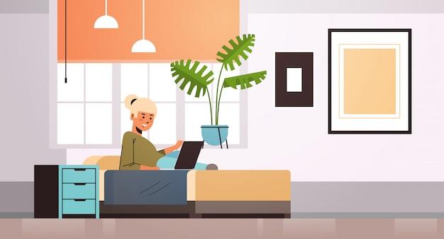 Vrouw freelancer met behulp van laptop thuis werken tijdens coronavirus quarantaine zelfisolatie freelance