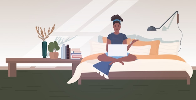 Vrouw freelancer zittend op bed met behulp van laptop verblijf thuis coronavirus pandemie quarantaine concept