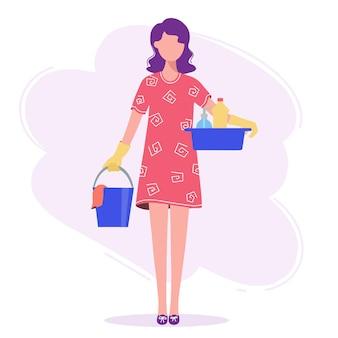 Vrouw gaat schoonmaken, in haar handen een emmer en een bak.