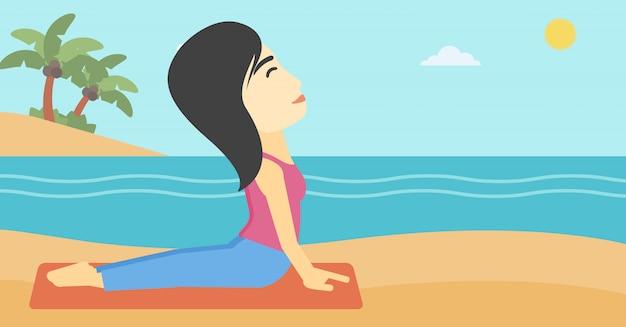 Vrouw het praktizeren de yoga stijgende hond stelt op strand.