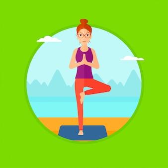 Vrouw het praktizeren de yogaboom stelt op het strand.