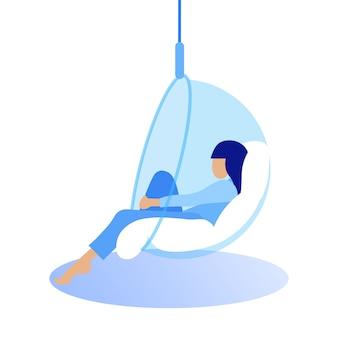 Vrouw in blauw shirt zit in glazen hangende stoel.