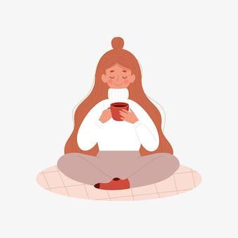 Vrouw in een warme trui drinkt koffie thee warme chocolademelk zittend op het tapijt