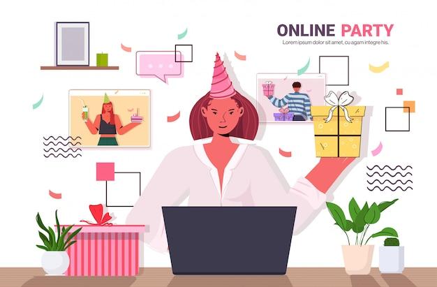 Vrouw in feestelijke hoed online verjaardagsfeestje vieren tijdens videogesprek