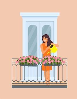 Vrouw is bloemen op het balkon water geven