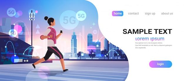 Vrouw joggen en luisteren naar muziek 5g high speed internet netwerk vijfde innovatieve generatie draadloze systemen verbinding concept stadsgezicht achtergrond vlakke horizontale volledige lengte kopie ruimte