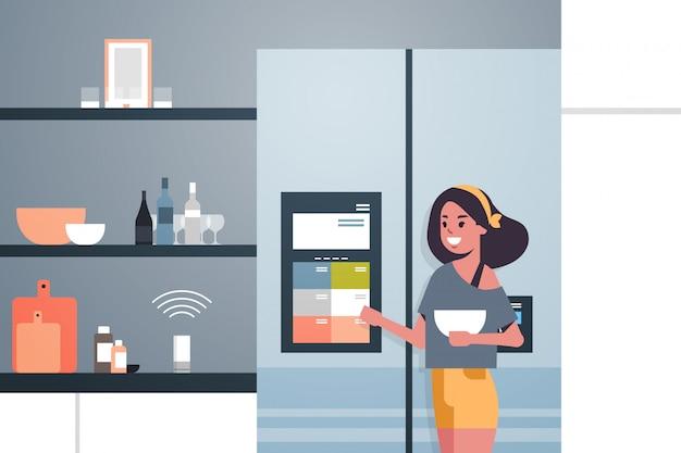 Vrouw koelkast scherm met slimme luidspreker spraakherkenning aan te raken
