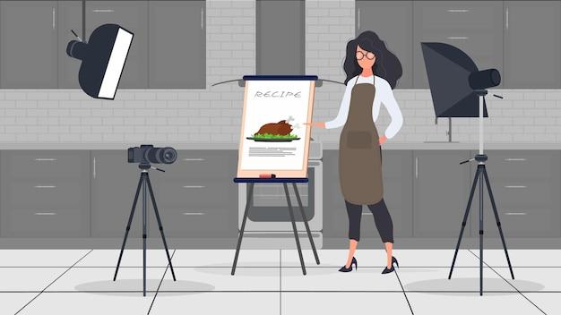 Vrouw kok in de keuken blijft een culinaire vlog leiden. een meisje in een keukenschort houdt een gebakken kip vast. vector.