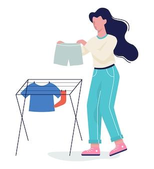Vrouw legde haar kleren te drogen op het touw. kleding aan de waslijn. t-shirt en sok, handdoek. illustratie in stijl