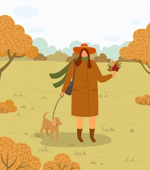 Vrouw lopen hond aan leiband in herfst bos park