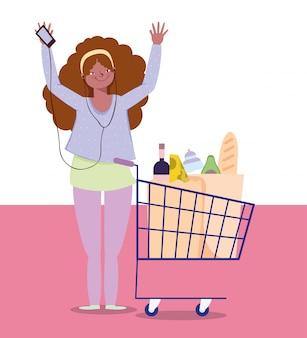 Vrouw luisteren muziek, winkelwagentje voedsel supermarkt