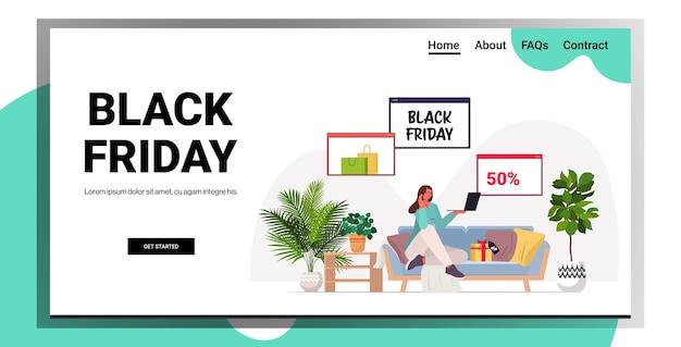 Vrouw met behulp van laptop online winkelen zwarte vrijdag grote verkoop vakantie kortingen concept woonkamer interieur kopie ruimte