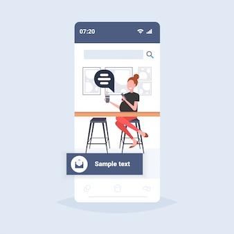 Vrouw met behulp van laptop praatjebel sociale media communicatieconcept meisje café bezoeker zit aan balie drinken koffie online toespraak gesprek smartphone scherm volledige lengte
