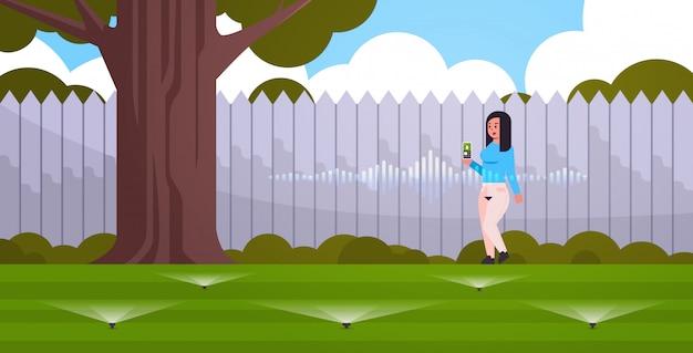 Vrouw met behulp van mobiele app controle irrigatie gras watergeefsysteem