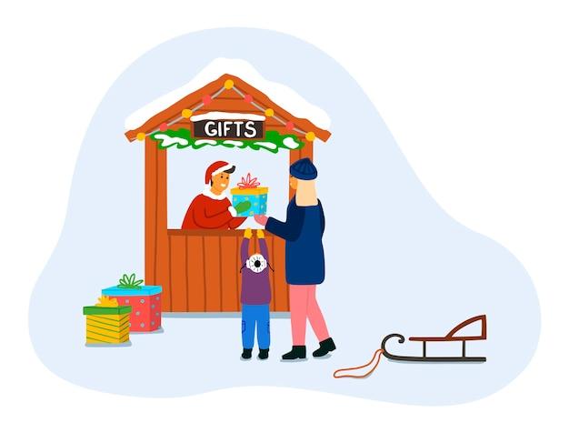 Vrouw met een kind koopt cadeautjes in een kiosk