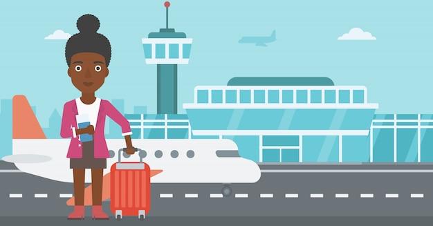 Vrouw met koffer en kaartje op de luchthaven.
