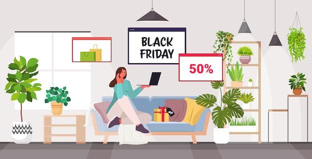 Vrouw met laptop online winkelen zwarte vrijdag grote verkoop vakantie kortingen concept woonkamer interieur