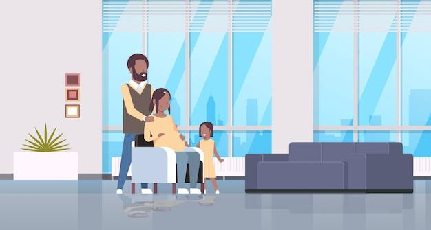 Vrouw met man en dochter gelukkig gezin thuis meisje moeder buik zwangerschap aan te raken en