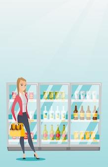 Vrouw met pakje bier in de supermarkt.