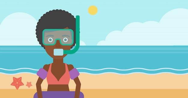 Vrouw met snorkeluitrusting op het strand.