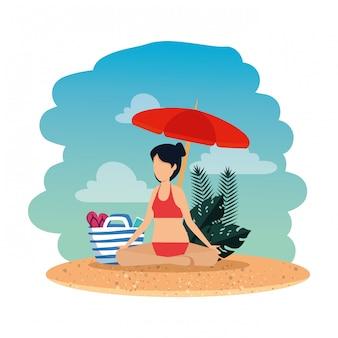 Vrouw met zwempak en paraplu beoefenen van yoga op het strand