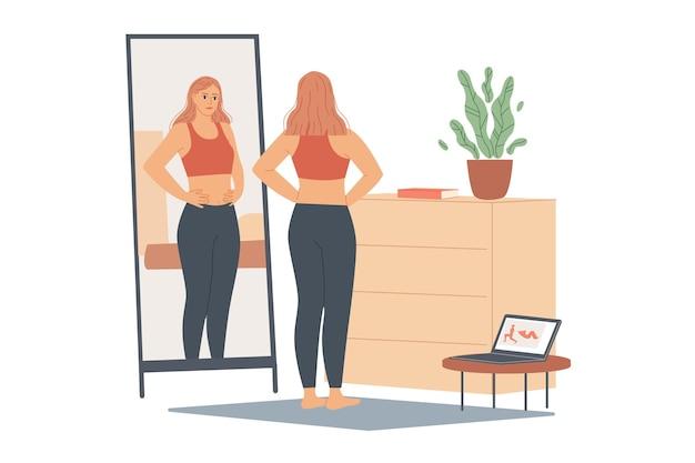 Vrouw niet blij met haar gewicht, ze kijkt naar haar buik en taille, staat voor een spiegel en kijkt naar haar lichaam na de training.