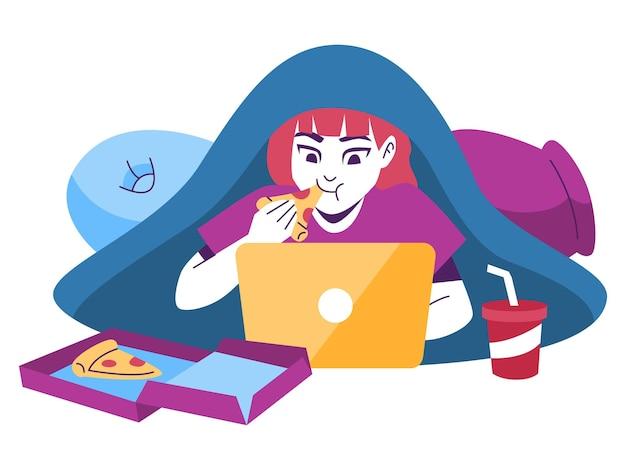 Vrouw onder een deken die pizza eet terwijl ze voor een lapto werkt