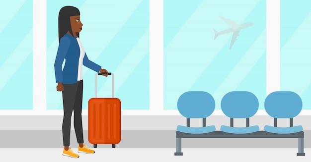 Vrouw op luchthaven met koffer