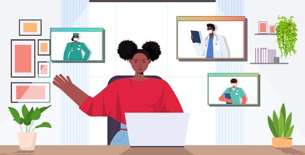 Vrouw patiënt bespreken met mix race artsen in webbrowser