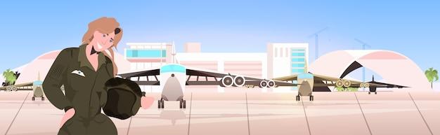 Vrouw piloot in uniform bedrijf helm luchthaven terminal met vliegtuigen luchtvaart concept portret