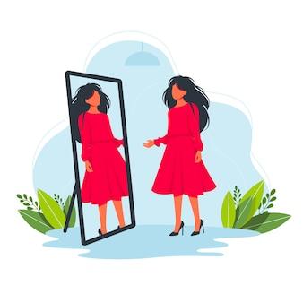 Vrouw probeert een mooie rode jurk in de winkel voor de spiegel. probeer op mode kleding concept. kleding passen.