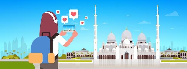Vrouw reiziger fotograferen nabawi moskee voortbouwend op smartphone camera live streaming