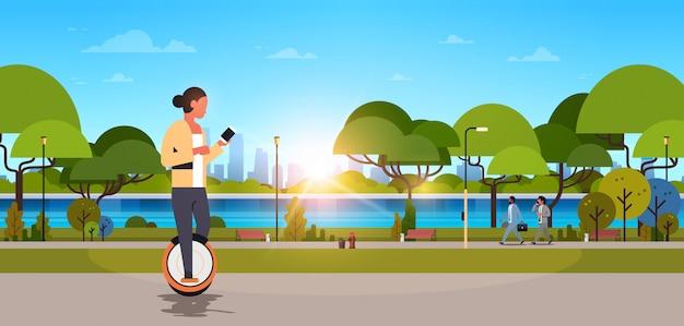 Vrouw rijden elektrisch monowiel met behulp van smartphone