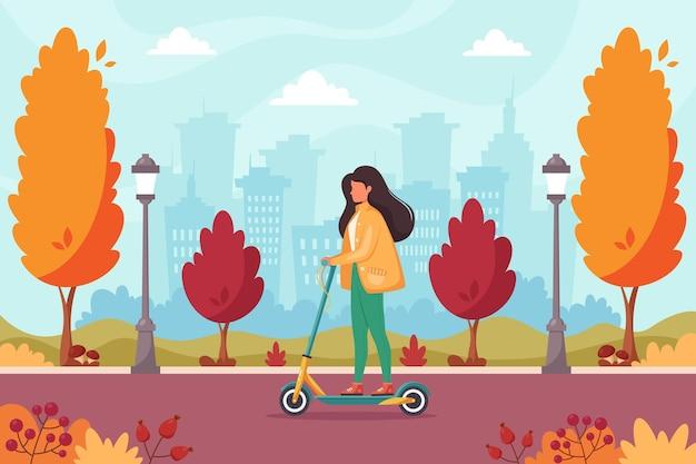 Vrouw rijden elektrische scooter in herfst park eco transport