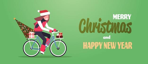 Vrouw rijden fiets met fir tree geschenkdoos voor kerst