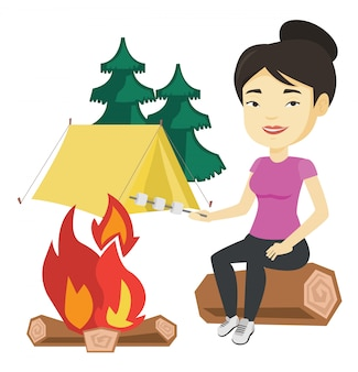 Vrouw roosteren marshmallow boven kampvuur.