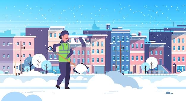 Vrouw schonere met behulp van plastic schop sneeuwruimen concept werkneemster in uniform schoonmaken woonwijk moderne stad gebouwen stadsgezicht vlak en horizontaal volledige lengte vectorillustratie