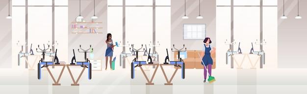 Vrouw schoonmakers afvegen glazen wand en vegende vloer mix race vrouwelijke conciërges werken samen schoonmaak service concept moderne open ruimte kantoor kamer interieur plat volledige lengte horizontaal