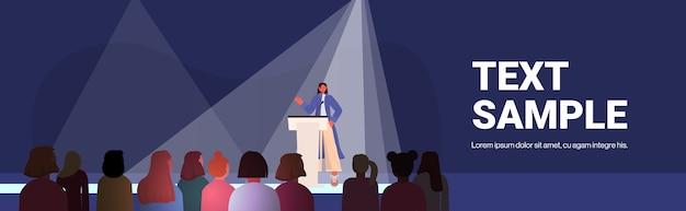 Vrouw spreekt tot publiek van tribune vrouwenclubmeisjes ondersteunen elkaar unie van feministen concept conferentiezaal interieur kopie ruimte