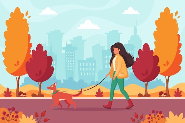 Vrouw wandelen met hond in herfst park
