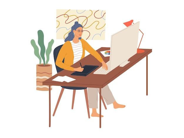 Vrouw werkt op haar computer met behulp van een grafisch tablet. een medewerker van het creatieve beroep.