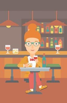 Vrouw zit aan de bar.