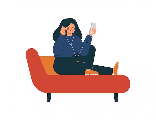 Vrouw zit op de bank en luistert naar muziek of audioboek met koptelefoon op haar telefoon
