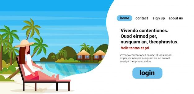 Vrouw zit zon bed lounge stoel op tropisch eiland villa bungalow hotel strand aan zee groene palmen landschap zomervakantie platte copyspace
