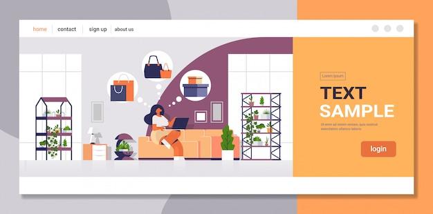 Vrouw zitten op de bank met laptop met behulp van computer applicatie online winkelen verkoop concept meisje kiezen aankopen moderne woonkamer interieur plat volledige lengte kopie ruimte