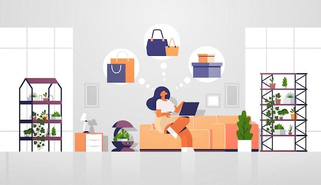 Vrouw zitten op de bank met laptop met behulp van computer applicatie online winkelen verkoop concept meisje kiezen voor aankopen moderne woonkamer interieur plat volledige lengte