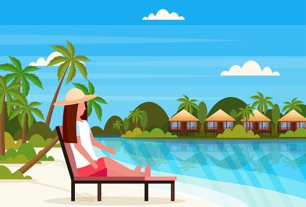 Vrouw zitten zon bed lounge stoel op tropisch eiland villa bungalow hotel strand aan zee groene palmen landschap zomervakantie plat
