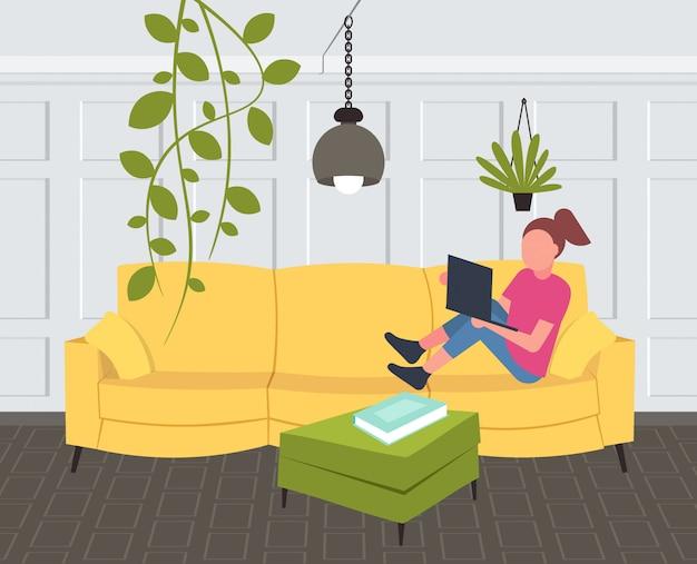 Vrouw zittend op bank meisje met behulp van laptop eigentijdse woonkamer interieur huis modern appartement horizontale volledige lengte